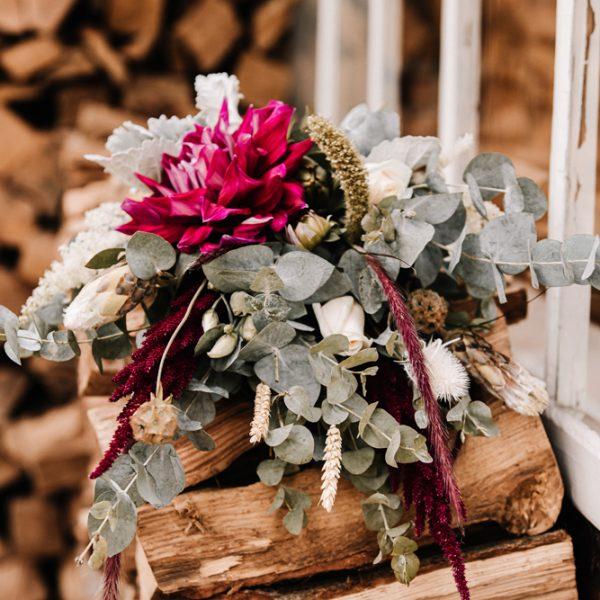 Blumenarrangement auf Holzstapel, Marion Flemming