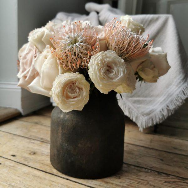 Protea und Rosen in einer Vase